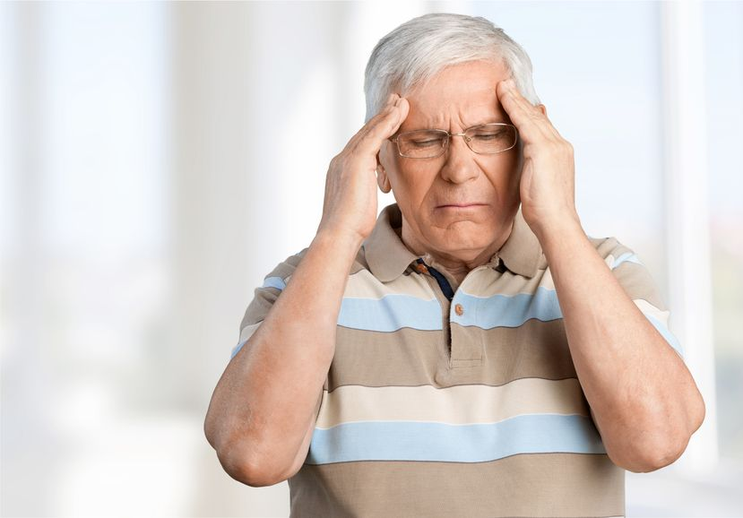an elderly man rubbing his temples because he's having a stroke