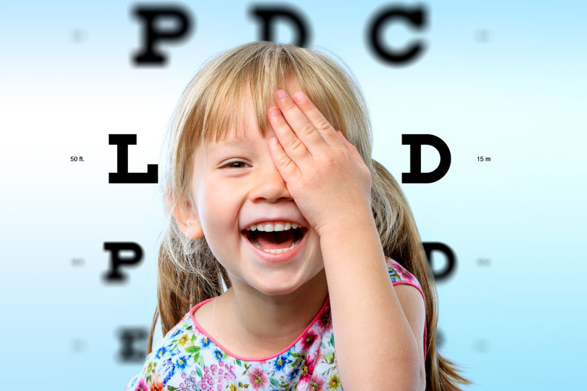 47634708 - close up face portrait of happy girl having fun at vision test.conceptual image with girl closing one eye with hand and block letter eye chart in background.