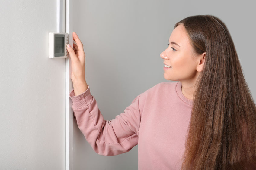Woman adjusting thermostat on white wall. Heating system