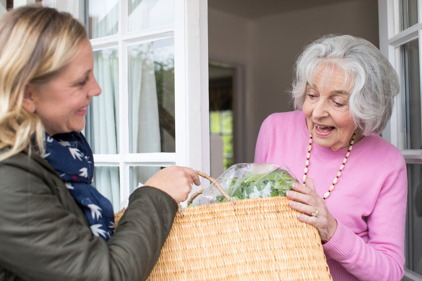 Female Neighbor Helping Senior Woman With Shopping