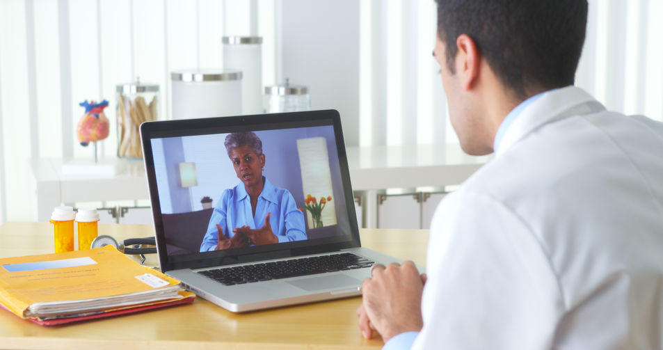Doctor video chatting with mature patient